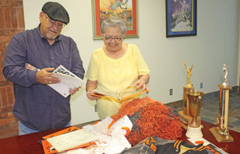 "FSIS Graduates Ron Burgess (left) and Rita Wahnee (right) look over items to be displayed as part of the ""Fort Sill Indian School - The Boarding School Experience"" exhibit at the Comanche National Museum and Cultural Center in Lawton. PHOTO COURTESY COMANCHE NATIONAL MUSEUM"
