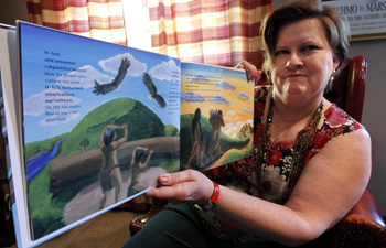 In this Aug. 5, 2011 photo, Brenda Lintinger poses with one of her children's books she wrote in the Tunica Indian language, in her home in Metairie, La. Lintinger decided to do more than learn a new language: she set out to resurrect the ancient tongue of her own Tunica Indian tribe, words that had not been uttered for more than 60 years. (AP Photo/Gerald Herbert)