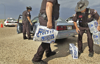 In this June 3, 2004, file photo, Pine Ridge police officers Mirian Laybad, left, Sgt. Oscar Hudspeth, center, and Lt. Mitch Wisecarver confiscate cases of beer at a checkpoint just north of Whiteclay, Neb. The Oglala Sioux Tribe announced Thursday, Feb. 6, that it will file a $500 million federal lawsuit against some of the nation's largest beer distributors, alleging that they knowingly contributed to the chronic alcoholism, health problems and other social ills on the Pine Ridge Indian Reservation. The lawsuit also targets the four beer stores in Whiteclay, a Nebraska town (pop. 11) on the South Dakota border that sells about 5 million cans of beer per year.   WILLIAM LAUER/LINCON JOURNAL STAR FILE PHOTO